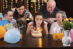 Happy family celebrating teenager girl anniversary. Happy family celebrating teenager daughter and granddaughter anniversary. The girl blows the candles on royalty free stock image
