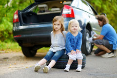 Happy family changing a car wheel Stock Images