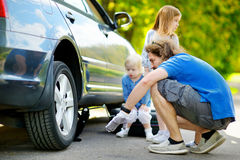 Happy family changing a car wheel Royalty Free Stock Photo