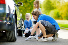 Happy family changing a car wheel Stock Photos