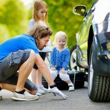 Happy family changing a car wheel Royalty Free Stock Photos