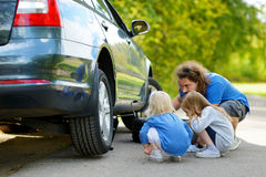 Happy family changing a car wheel Royalty Free Stock Image