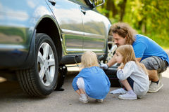 Happy family changing a car wheel Stock Image