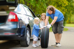 Happy family changing a car wheel Royalty Free Stock Images