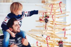 Happy family, father and son decorate handcrafted christmas tree made of driftwood at home. Happy family, cheerful father and son decorate handcrafted christmas royalty free stock photos