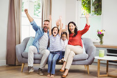 Happy family cheering while siting on sofa royalty free stock images