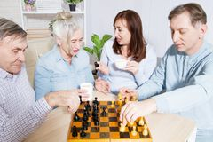 Happy family chess game time at nursing home for elderly. Parents with children have fun talk and leisure. Senior couple. And relatives. Visit old mother father stock photos