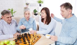 Happy family chess game time at nursing home for elderly. Parents with children have fun talk and leisure. Senior couple. And relatives. Visit old mother father royalty free stock photography