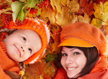Happy family with child on autumn orange leaves. royalty free stock photo
