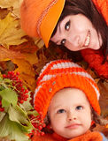 Happy family with child on autumn orange leaves. Happy family with child on autumn orangeleaves. Outdoor royalty free stock photo