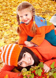 Happy family with child on autumn orange leaves. stock photos