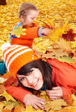 Happy family with child on autumn orange leaves. Royalty Free Stock Images