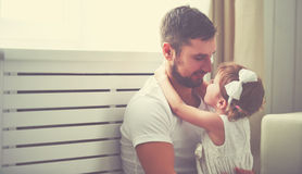 Happy family child baby girl in arms of his father at home stock photo