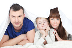Happy family with child in bed Royalty Free Stock Photo