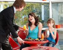 Happy family with child in cafe. Stock Images