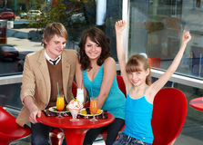 Happy family with child in cafe. Royalty Free Stock Images
