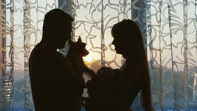 Happy family with a child and a dog. Standing at the window, my father keeps on hand a dog stock footage