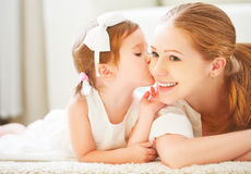 Happy family. Child girl kisses her mom Stock Images