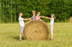 Happy family with child on haystack in sunny day Stock Images