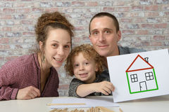 Happy family, child holding paper with drawing house. Happy family, child holding paper with drawing a house royalty free stock photo