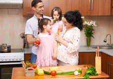 Happy family with child in home kitchen interior with fresh fruits and vegetables, pregnant woman, healthy food concept Royalty Free Stock Image