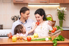 Happy family with child in home kitchen interior with fresh fruits and vegetables, pregnant woman, healthy food concept Royalty Free Stock Images
