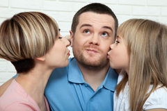 Happy family with child at home. Mother and daughter kissing daddy close up. Stock Photos