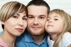Happy family with child at home. Mother and daughter kissing daddy close up. Royalty Free Stock Photos