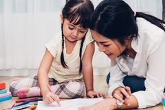 Happy family child kid girl kindergarten drawing teacher educati. On mother mom with beautiful mother at interior room home stock photo