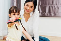 Happy family child kid girl kindergarten show crayon teacher education with beautiful mother stock images