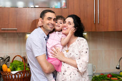 Happy family with child in kitchen interior with fresh fruits and vegetables, pregnant woman, healthy food concept Stock Image