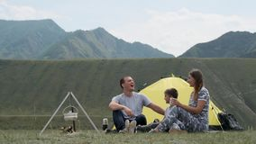 Happy family with a child laughing on campsite near a tent with a bonfire. Happy young family of tourists with a child laughing on campsite near a tent with a stock video footage