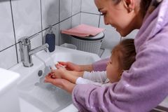 Happy family - child and mother washing hands with soap in bathroom. Happy family - child and mother washing hands with soap in bathroom at home stock photos