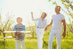 Happy family with a child outdoors in summer. Mother, father and son with a plane playing in the park stock photography