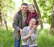 Happy family and child portrait. City park in summer season. Beautiful landscape with trees and green grass Royalty Free Stock Photo