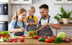 Happy family with child  preparing vegetable salad Stock Images