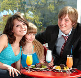 Happy family with child in restaurant. Stock Photography