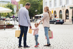 Happy family with child and shopping bags in city. Sale, consumerism and people concept - happy family with little child and shopping bags in city stock photos