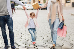 Happy family with child and shopping bags in city. Sale, consumerism and people concept - happy family with little child and shopping bags in city royalty free stock photo