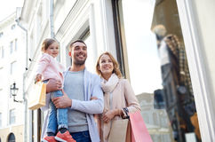 Happy family with child and shopping bags in city. Sale, consumerism and people concept - happy family with little child and shopping bags in city Royalty Free Stock Image