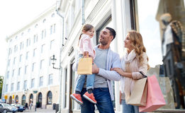Happy family with child and shopping bags in city. Sale, consumerism and people concept - happy family with little child and shopping bags in city Stock Photo