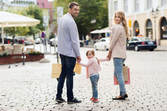 Happy family with child and shopping bags in city. Sale, consumerism and people concept - happy family with little child and shopping bags in city stock photography
