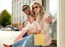 Happy family with child and shopping bags in city Stock Image