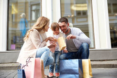 Happy family with child and shopping bags in city. Family, sale, consumerism and people concept - happy mother , father and little child with shopping bags Royalty Free Stock Image