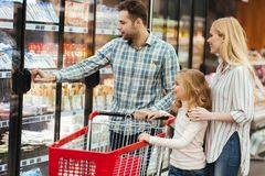 Happy family with child and shopping cart buying food. At grocery store or supermark Stock Photo