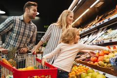 Happy family with child and shopping cart buying food. At grocery store or supermark royalty free stock photo
