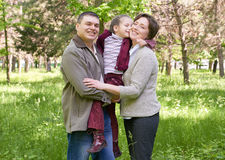 Happy family and child in summer park, beautiful landscape with trees and green grass Royalty Free Stock Photos