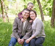 Happy family and child in summer park, beautiful landscape with trees and green grass Royalty Free Stock Photo