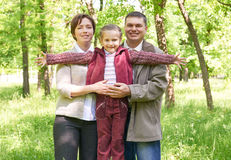Happy family with child in summer park, sunlight, green grass and trees Stock Image