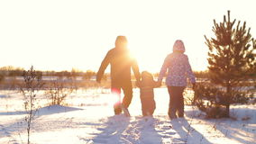 Happy family with a child walking in the snow at sunset stock footage